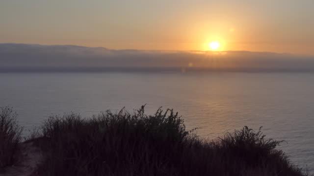 vídeos de stock, filmes e b-roll de sun rays through a fog bank as the sun is setting - califórnia