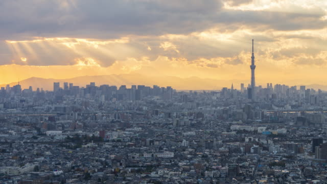 sun rays through clouds over tokyo skyline - tokyo japan stock videos and b-roll footage