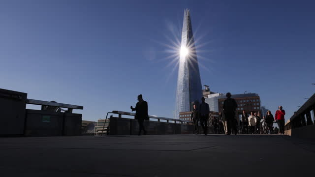 sun reflected in the shard skyscraper and silhouettes of morning commuters crossing london bridge in london, u.k. on thursday, may 27, 2021. - surface level stock videos & royalty-free footage