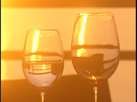 sun reflecting in wine glasses during golden hour - wine glass stock videos & royalty-free footage