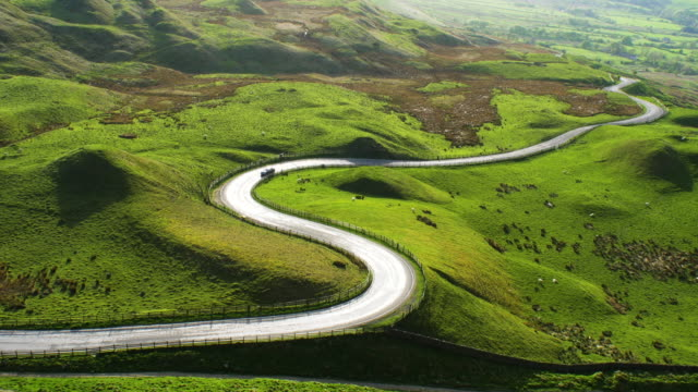 Sun reflecting on spectacular curving road in the English Peak District