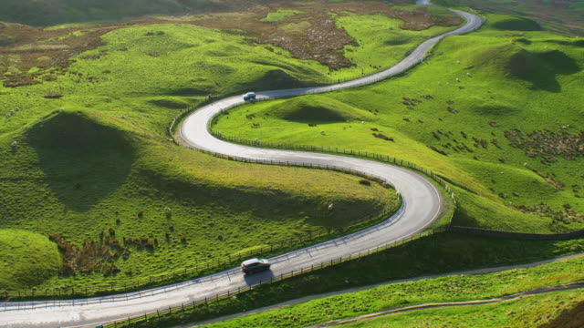 sun reflecting on spectacular curving road in the english peak district - winding road stock videos & royalty-free footage