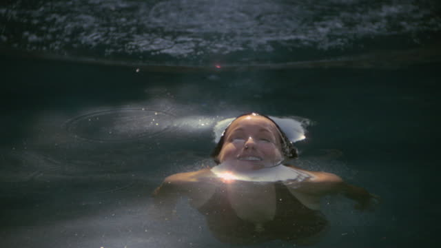 SLO MO MS Sun reflecting on woman surfacing from water/ California, USA
