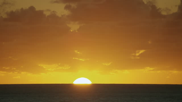 stockvideo's en b-roll-footage met sun rises above ocean horizon at sunrise - zonsopgang