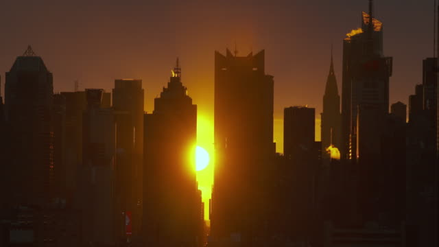 Sun rises behind a cluster of Manhattan Skyscrapers