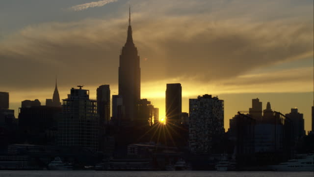 sun rises behind empire state building as ferry moves by along hudson river - establishing shot点の映像素材/bロール