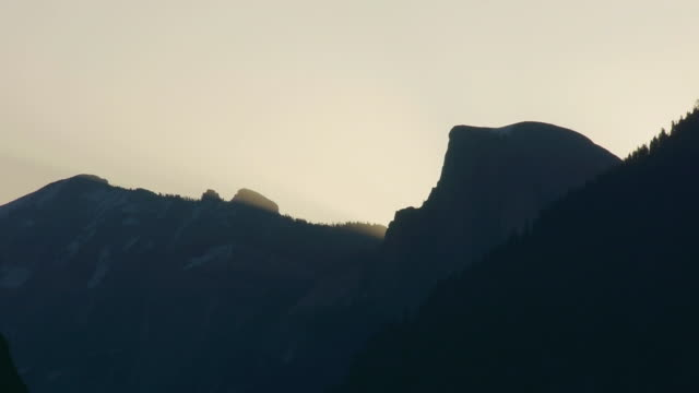 t/l sun rises behind half dome with sierra nevada mountain range behind, in yosemite national park, california - nevada stock-videos und b-roll-filmmaterial