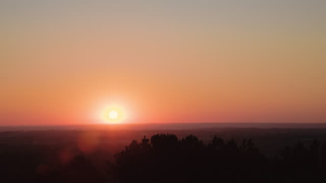 Sun rises on a vast horizon in a time lapse shot with an orange sky.