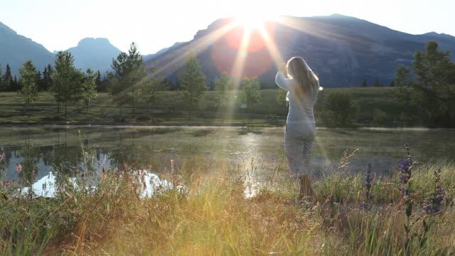 vídeos de stock, filmes e b-roll de sun rises over ridge crest as woman takes picture - só mulheres jovens