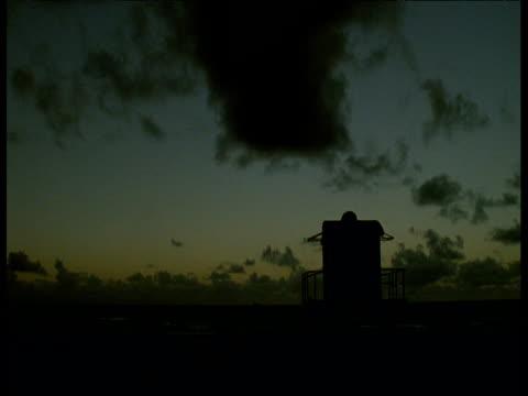 sun rises over sea behind lifeguard hut, miami beach - cabina del guardaspiaggia video stock e b–roll