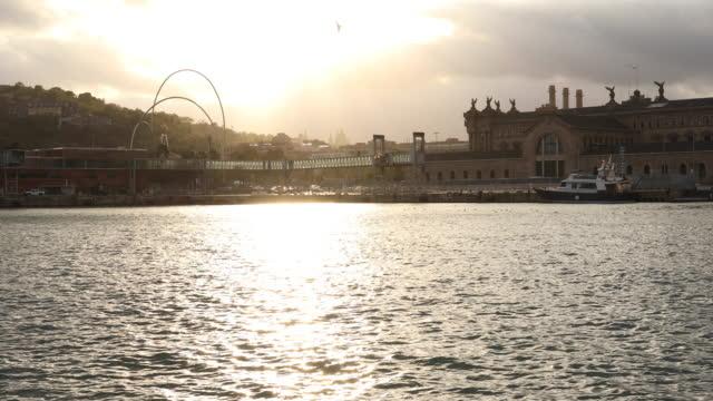 vídeos y material grabado en eventos de stock de el sol se levanta sobre la zona del puerto marítimo de la ciudad, barcelona - monumento
