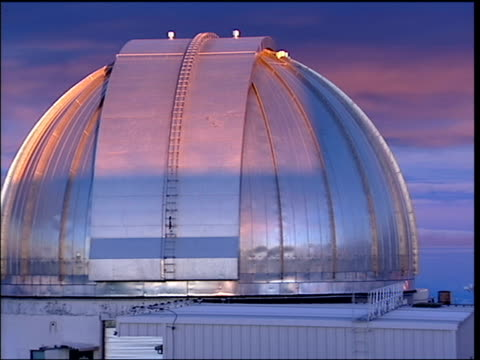 Sun rises over silver observatory roof
