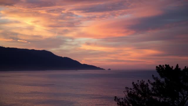 Sun rises through colorful skies on ocean coast