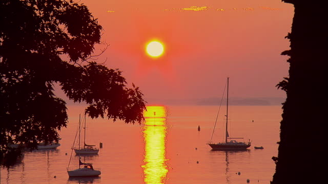 WS, Sun rising above harbor with moored sailboats, Camden, Maine, USA