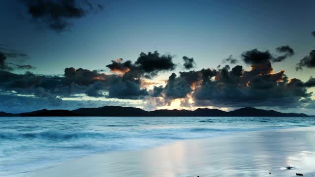 vídeos y material grabado en eventos de stock de sun rising and racing clouds over triopical beach at sunrise - seychelles