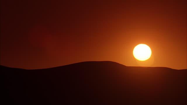 ws, sun rising behind hills / california - palm springs california stock videos & royalty-free footage
