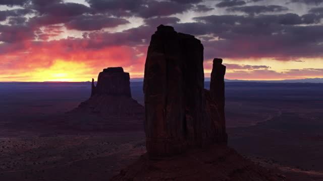 vídeos de stock, filmes e b-roll de sun que levanta-se atrás do vale do monumento mitten buttes no nascer do sol-aéreo - mitten