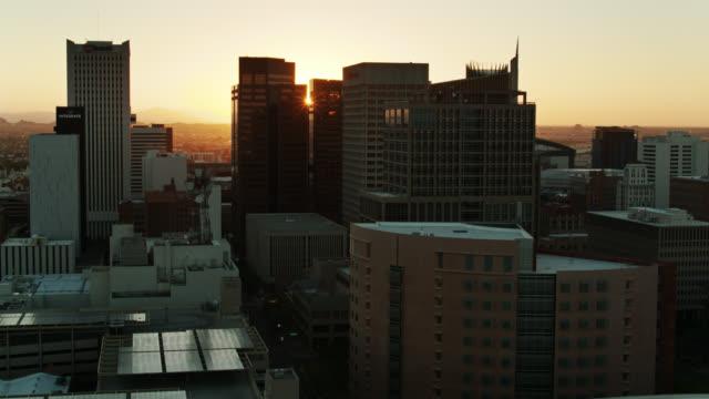 stockvideo's en b-roll-footage met sun rising achter phoenix wolkenkrabbers-bovenaanzicht - boven
