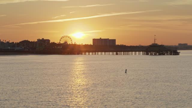 sun rising behind santa monica pier - santa monica pier stock videos & royalty-free footage