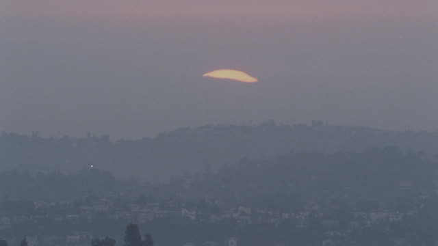 Sun rising from behind gray cloud fog smog covered hills houses FG Air pollution gasoline gas fossil fuel emissions Greenhouse gases Global Warming