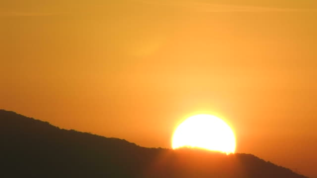 t/l sun rising from behind mountain - sunlight点の映像素材/bロール