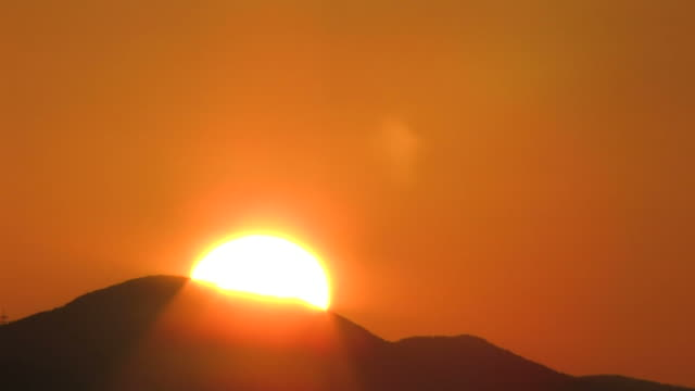 T/L WS Sun rising from behind mountain