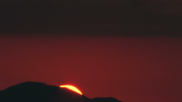 T/L Sun rising from behind mountain