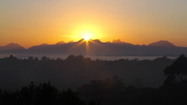 sun rising from behind mountain with low clouds - horizon over land stock videos & royalty-free footage