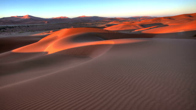sun rising on rippled sand dunes of sossusvlei - sand dune stock videos & royalty-free footage