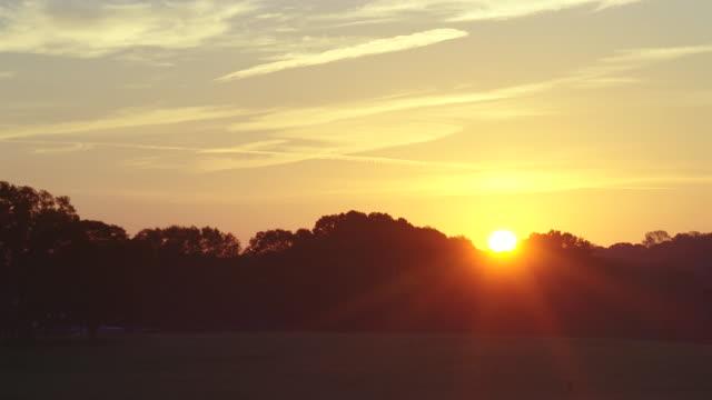 sun rising over farmland & trees - ländliches motiv stock-videos und b-roll-filmmaterial