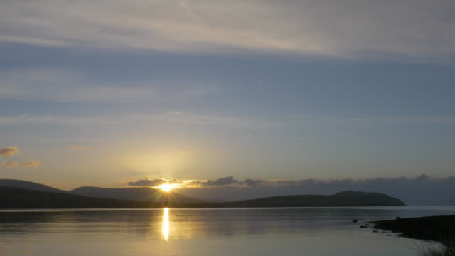 Sun rising over harbor, reflections on water, Kilfarnoge, County Kerry, Ireland