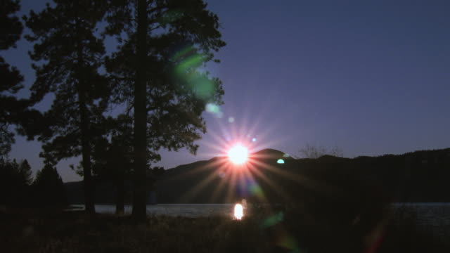 WS Sun rising over hill and sunbeams radiating over lake and sky