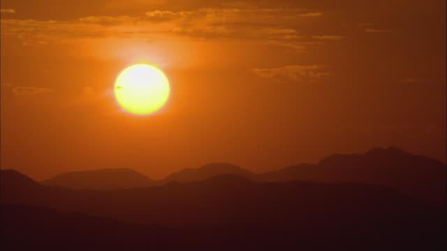 t/l ws sun rising over hills of mojave desert / california, usa - deserto mojave video stock e b–roll