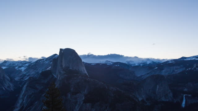 sun rising over the landscape of yosemite national park with glacier point and half dome - half dome stock videos & royalty-free footage