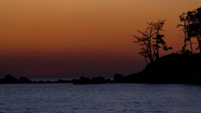 sun rising up with omega shape reflection in myeongseondo island / uljin-gun, ulsan, south korea - omega sun mirage stock videos & royalty-free footage