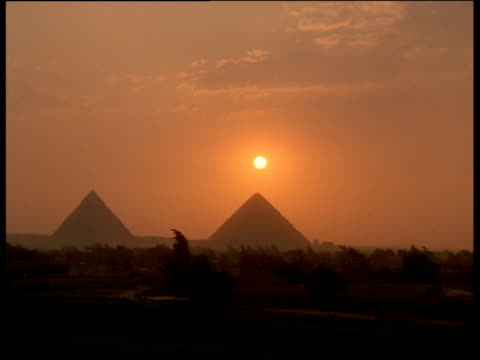 Sun sets above point of pyramid silhouetted against hazy and orange dusk sky