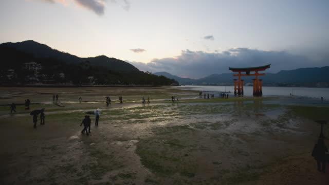 ws t/l sun sets as tide rises over itsukushima shrine's sacred torii gate in miyajima island / miyajima, hiroshima prefecture, japan - bassa marea video stock e b–roll