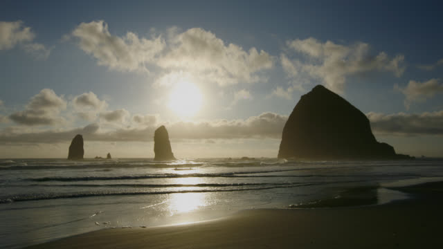 time lapse wide shot sun sets behind clouds over ocean with silhouetted boulders in water, cannon beach, oregon - cannon beach stock videos & royalty-free footage