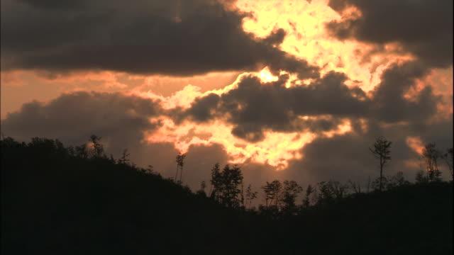 sun sets behind grey clouds above hills, muroto, japan - satoyama scenery stock videos & royalty-free footage
