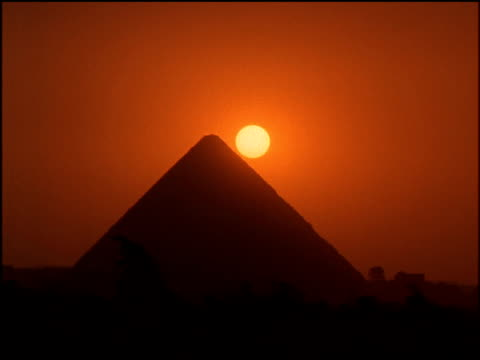 sun sets behind large silhouetted egyptian pyramid sky tinted orange - 幻想点の映像素材/bロール