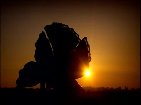 sun sets behind maggi hambling's scallop memorial to benjamin britten on aldeburgh beach suffolk - wirbelloses tier stock-videos und b-roll-filmmaterial
