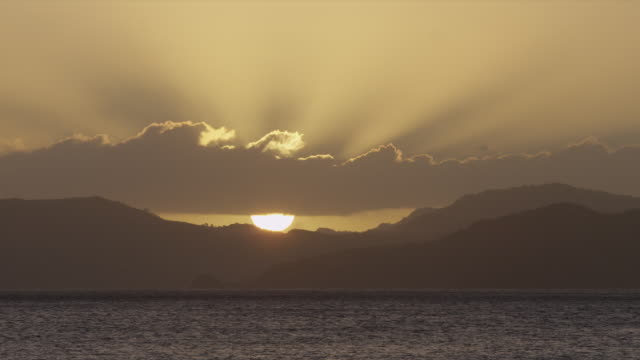 sun sets behind mountains giving off sun rays, ocean in foreground - 1 minute or greater stock videos & royalty-free footage