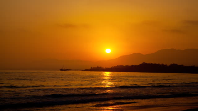 WS T/L Sun sets behind mountains over ocean waves coming to shore / Santa Barbara, California, United States
