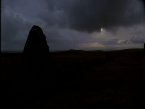 sun sets behind standing stone and storm clouds - dartmoor stock videos & royalty-free footage