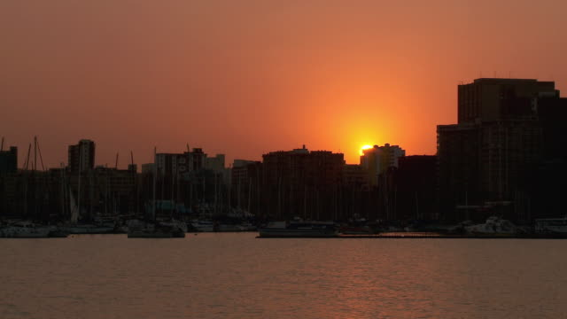 ws sun sets below durban skyline / durban, south africa - durban stock videos and b-roll footage