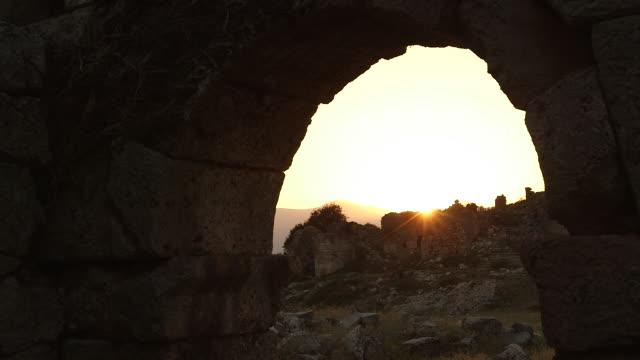 vídeos de stock e filmes b-roll de sun sets in arch of stone wall ruins turkey - wiese