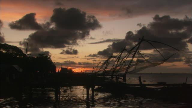 vídeos de stock e filmes b-roll de sun sets over chinese cantilever fishing nets available in hd. - rede de pesca comercial
