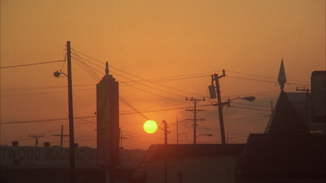ws sun setting above town against orange sky with power lines - town stock videos & royalty-free footage