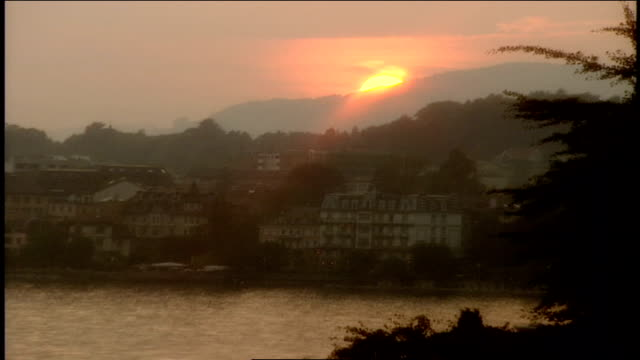 sun setting behind a mountain in montreux, switzerland - montreux stock videos & royalty-free footage