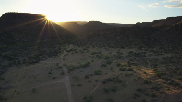 sun setting behind arizona mesas - drone shot - arizona stock-videos und b-roll-filmmaterial